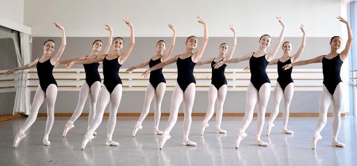 Tjejer i vita strumpbyxor och svart body dansar balett