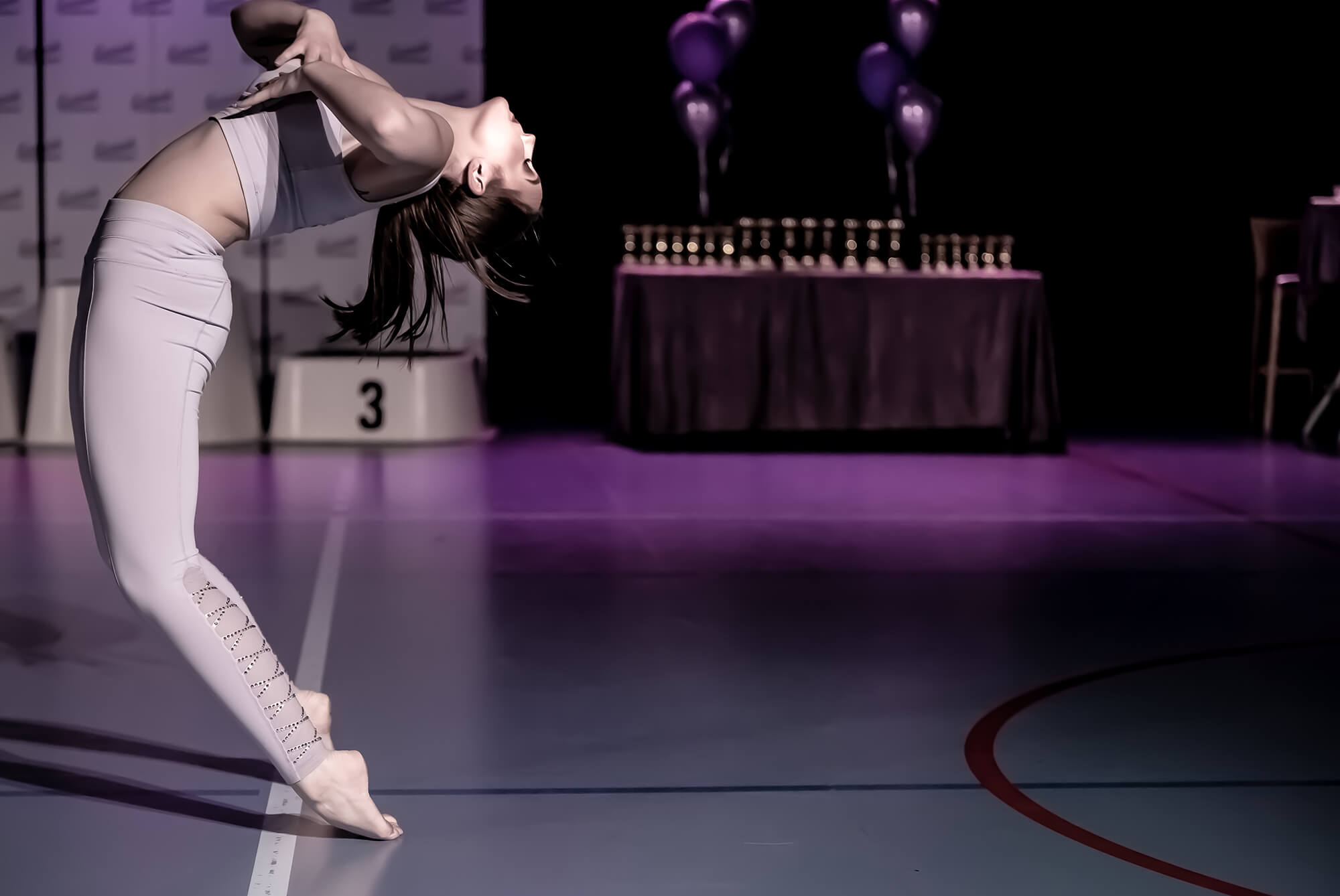 Tjej står på tå bakåtlutad i dans