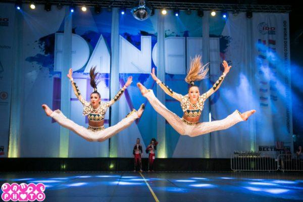 Två tjejer i vita kläder hoppar i split