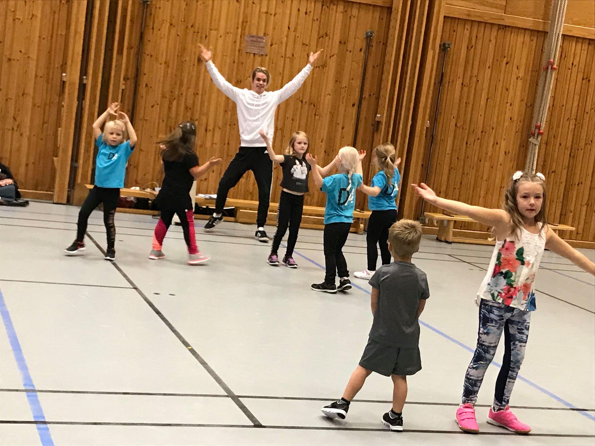 Barn dansar i en hall med en lärare