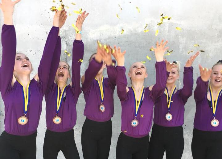 Personer i lila tröjor med medaljer