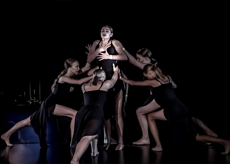 Tjejer dansar dramatiskt i svarta klänningar
