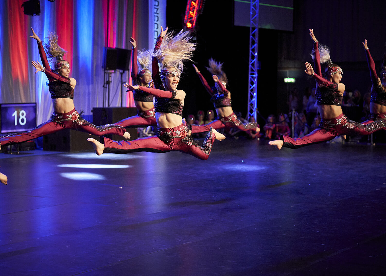 Tävlingsdansare i rött hoppar i split