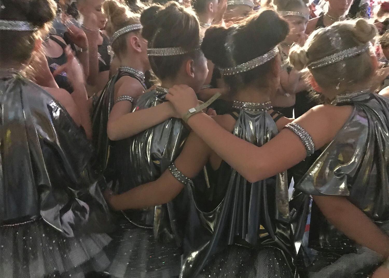 Tävlingsdansare i silvrigt håller om varandra