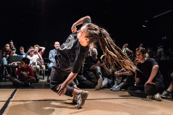 Person dansar breakdance framför publik