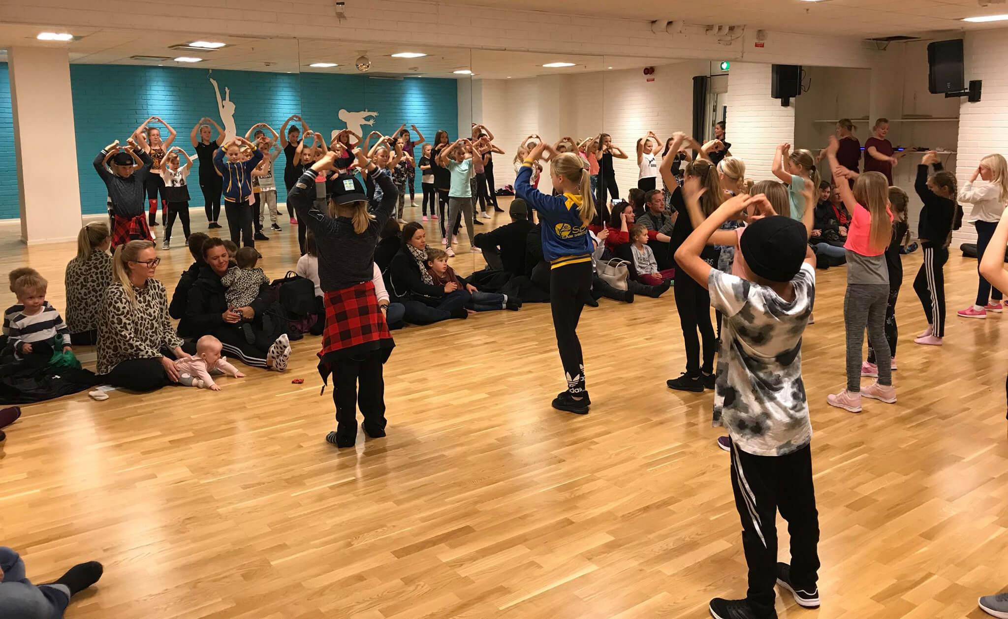 Barn dansar framför spegel och föräldrar