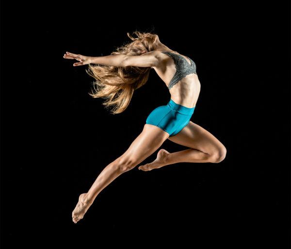 Kvinna i underkläder hoppar högt i en dans