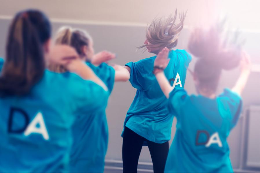 Ungdomar i blå tröjor dansar