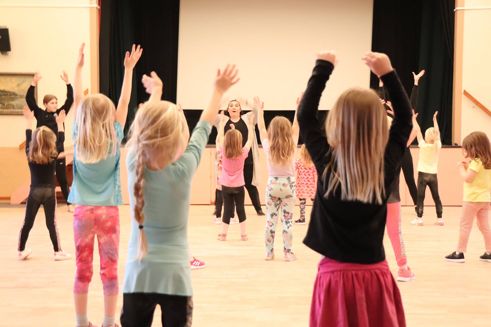 Barn dansar framför lärare