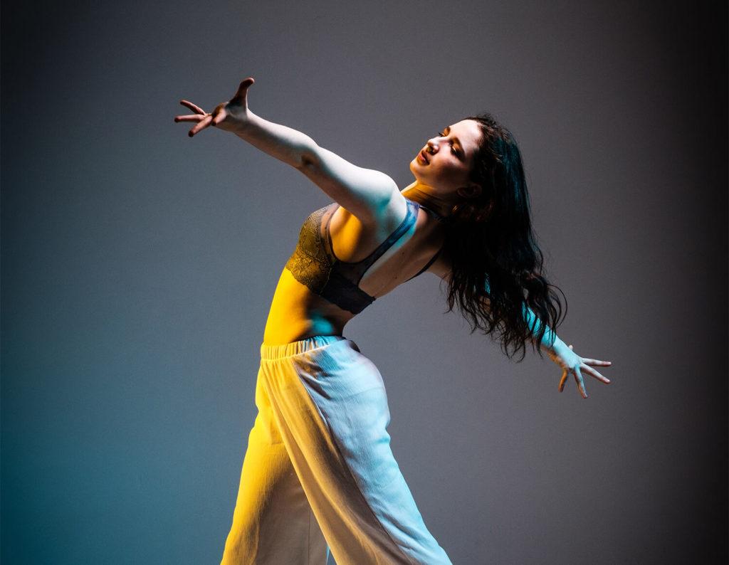 Kvinna i byxor och top sträcker ut händerna i dans