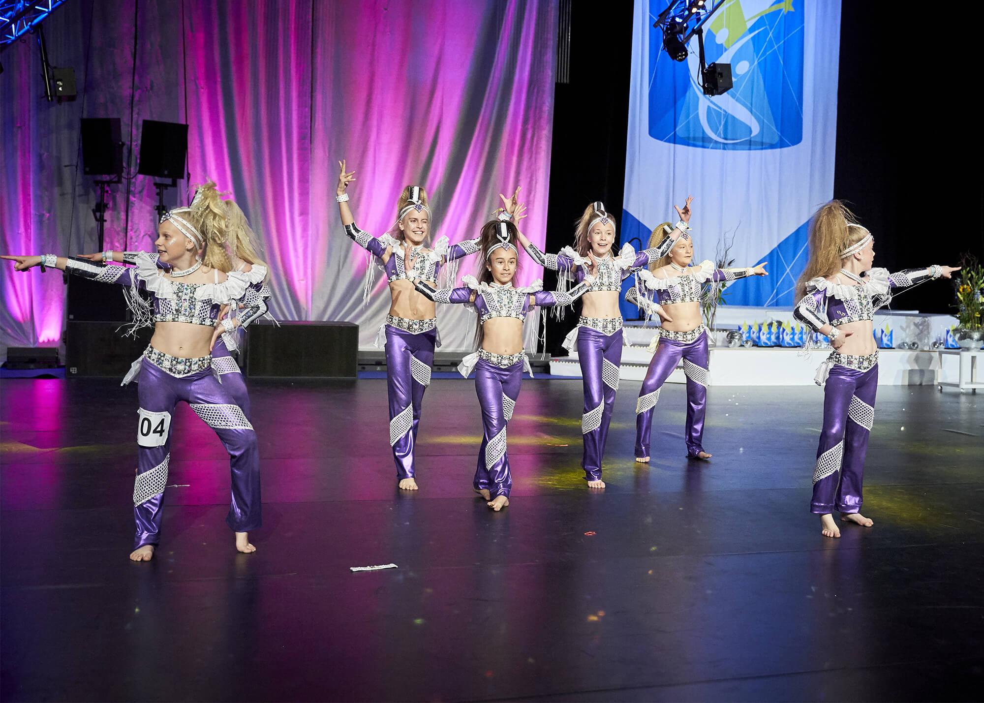 Tjejer i vita och lila kläder tävlingsdansar